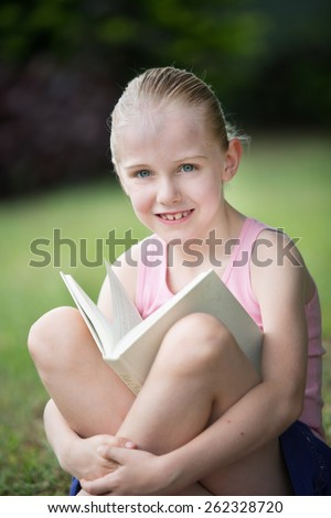 A young 7 year old girl relaxing with her white book outdoors.  She is relaxed studying or reading a novel.   - stock photo