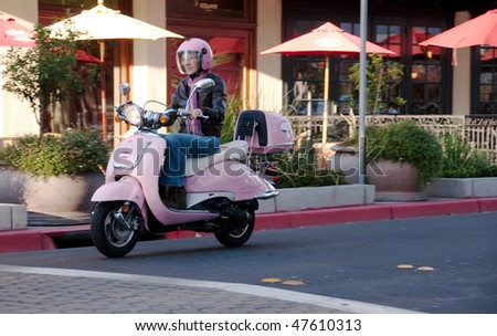 a youthful senior on her pink motorbike on a city street - stock photo