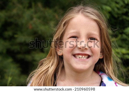 A youthful six year old smiles happily while playing outdoors in the summertime. - stock photo