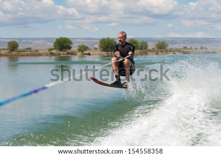 A 50 yr. old man jumps the wake as he slalom waterskis on Sweitzer Lake in Delta, Colorado. - stock photo