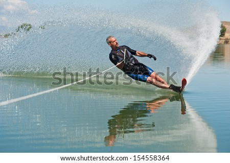 """A 50 yr. old man slalom waterskiing on Sweitzer Lake in Delta, Colorado. He is carving the water with his ski as he makes a turn, creating a """"rooster tail"""" of water. - stock photo"""