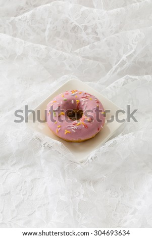 A yummy doughnut on a white background. This sweet photo would work well for bakeries, restaurants, food magazines, children's food, advertisements, greeting cards, or many other ideas and concepts. - stock photo