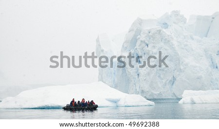 A zodiac boat filled with people looking at a massive iceberg in a snow storm - Antarctica - stock photo