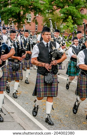 AABENRAA, DENMARK - JULY 6 - 2014: Scottish bagpipe band is marching down the street at the annual tilting festival in Aabenraa