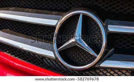 AACHEN, GERMANY FEBRUARY, 2017: Mercedes Benz logo on a red car grill. Mercedes-Benz is a German automobile manufacturer. The brand is used for luxury automobiles, buses, coaches and trucks.