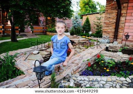 Aadorable brunette kid girl, watering the plants, from hose spray in the garden at the backyard of the house on a sunny summer evening - stock photo