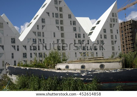 AARHUS, DENMARK - JULY 13, 2016: New modern architecture on Aarhus harbor. The buildings called The Iceberg. View from City Gardenwith vintage wooden boat. July 13, 2016. - stock photo