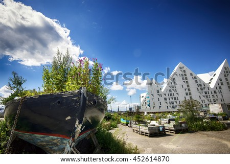 AARHUS, DENMARK - JULY 13, 2016: New modern architecture on Aarhus harbor. The buildings called The Iceberg. View from City Garden with vintage wooden boat. July 13, 2016. - stock photo