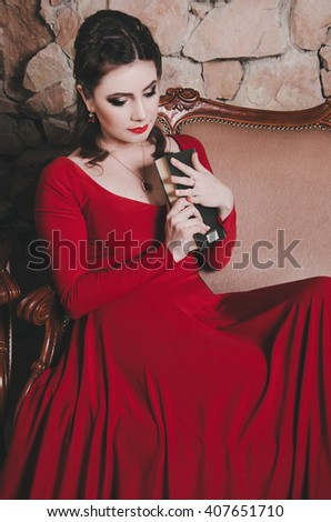 Aattractive brunet 30 year old woman with makeup, hairstyle, jewelry, long red evening dress holding classic book, sitting on armchair sofa, thoughtfully looking. Portrait female in vintage interior. - stock photo