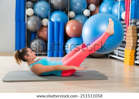 Ab exercise woman swiss ball leg lifts Pilates workout abs at gym - stock photo