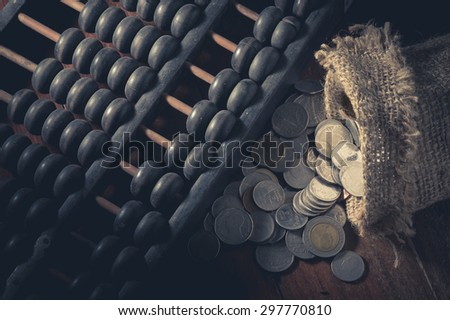 Abacus with coins in gunny sack,vintage filtered. - stock photo