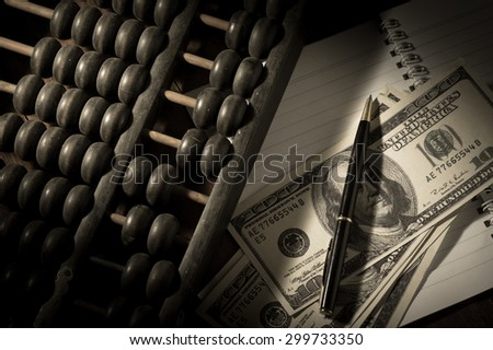 Abacus with pen and money on book. - stock photo