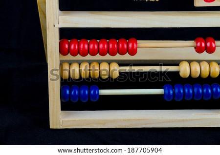 abacus, wood, black background - stock photo