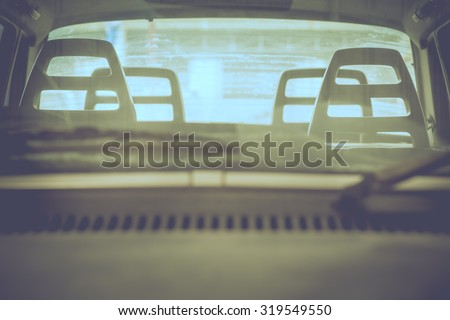 Abandon broken car looking through windshield  with selective focus on head rest of the driver seat in vintage tone. - stock photo