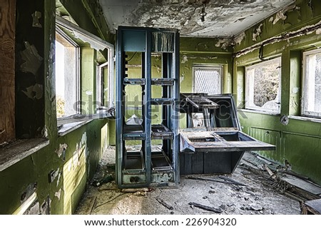 Abandoned and destroyed room with a printing machine