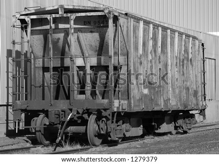 Abandoned and rusting agricultural use hopper rail car.  Situated on side track next to unused warehouse. - stock photo