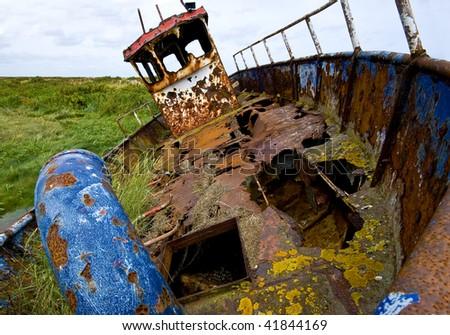 Abandoned and rusting fishing boat in Blakeney salt marsh, UK. - stock photo