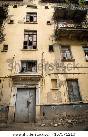 Abandoned apartment building with stained walls and broken windows - stock photo