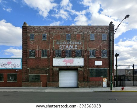Abandoned boarding stable brick building with pig painting - landscape color photo - stock photo