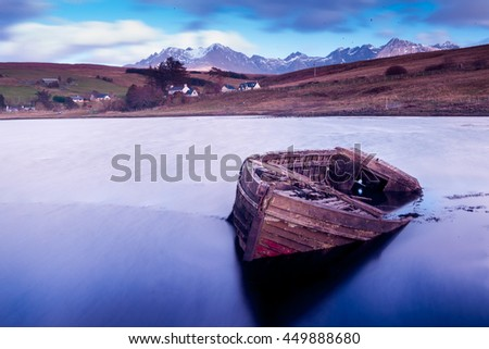 Abandoned boat in a beautiful lake - stock photo