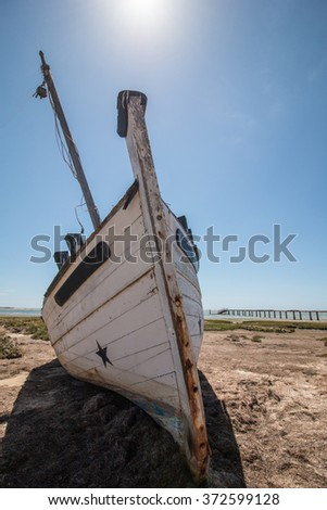 Abandoned boat on the vegetation on the sand dunes of Ria Formosa marshlands located in the Algarve, Portugal. - stock photo