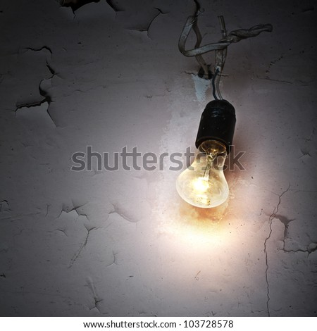 abandoned bright bulb on dirty old squat wall