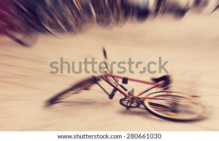 Abandoned broken bike laying on the ground in the middle of the city, defocused with radial zoom, instagram retro filter applied in postprocessing - stock photo