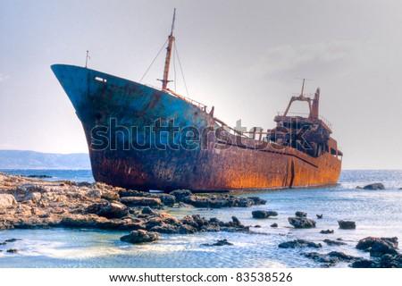 Abandoned broken ship-wreck beached on rocky sea shore. - stock photo