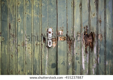 Abandoned  broken wooden shed door and lock.