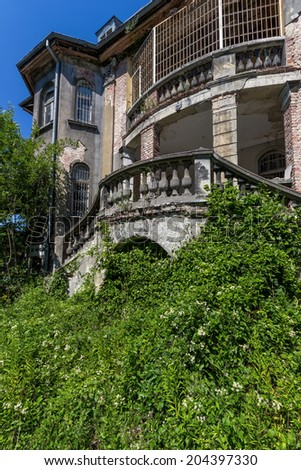 Abandoned building covered with vegetation - stock photo