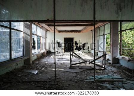 Abandoned building interior. Hall perspective with dirt on the floor and broken windows - stock photo