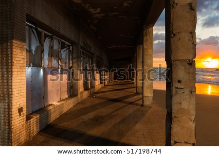 abandoned building on the beach with sunset