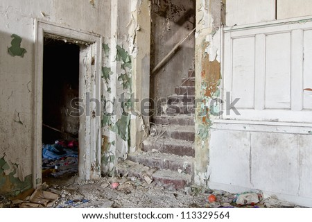 Abandoned building with peeling paint and crumbling walls. - stock photo
