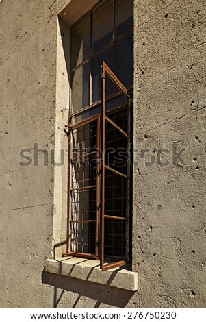 Abandoned building with rusty window frame open