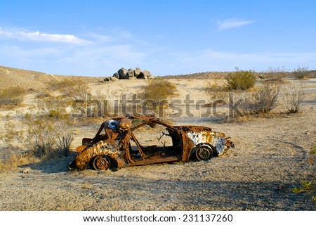 Abandoned car left to rust and be used as target practice sits on its axel. - stock photo