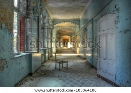 Abandoned chair in an old corridor - stock photo