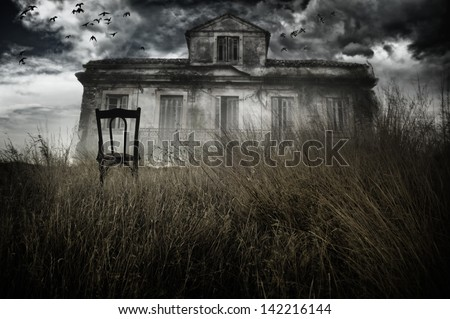 Abandoned chair out in a field facing a haunted house - stock photo