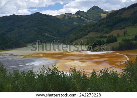 Abandoned church in the middle of a red polluted lake full with mining residuals in Romania, Alba, Geamana - stock photo