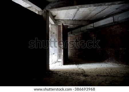 Abandoned construction dark. Light falls on a concrete floor - stock photo