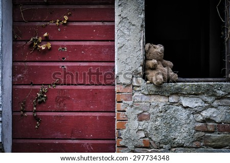 abandoned damaged toy on a broken window near an old red door. Location: ghost town of Buriano, Pisa, Tuscany, Italy. - stock photo