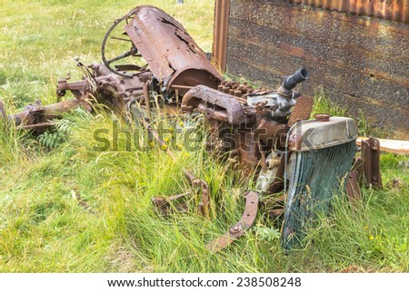 Abandoned derelict tractor in advanced stage of rusting to pieces