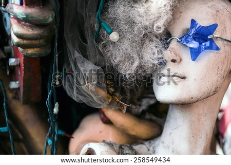 Abandoned dirty mannequin head surrounded by junk. - stock photo