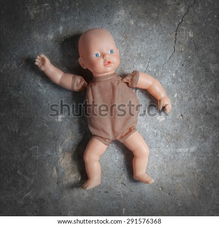 Abandoned doll laying on a concrete floor - stock photo