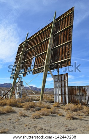 Abandoned drive-in screen in desert against blue sky - stock photo
