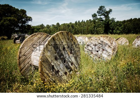 Abandoned electric cable reels in a paintball battle field - stock photo