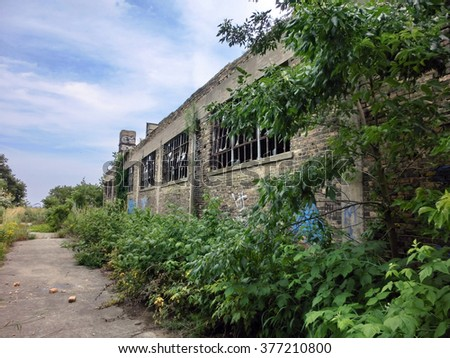 Abandoned factory warehouse exterior with overgrown plants - landscape color photo - stock photo