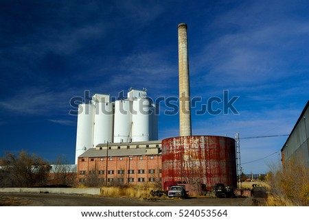 Abandoned Factory with Storage Tanks, Smokestack, and an Agriculture Grain Elevator Silo in the Background