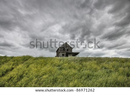 Abandoned Farm with storm clouds in the Canadian Prairie - stock photo