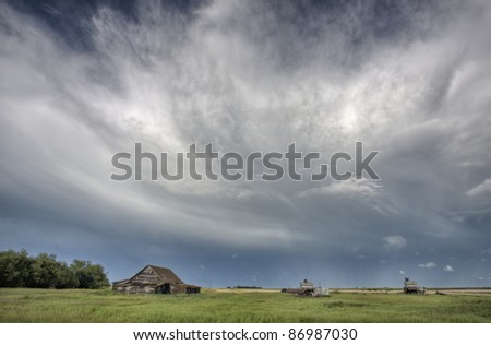 Abandoned Farm with storm clouds in the Canadian Prairie