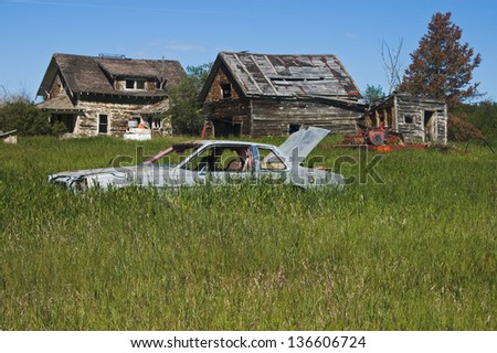 abandoned farmyard with old car in foreground - stock photo